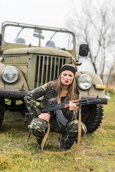 Mulher de uniforme militar com rifle e carro