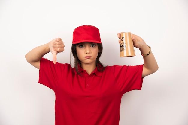 Mulher de uniforme vermelho com copo vazio mostrando o polegar para baixo