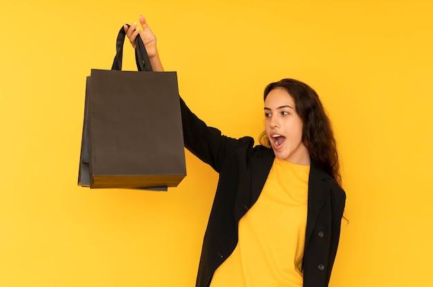 Mulher de vendas com sacola de papel preto.