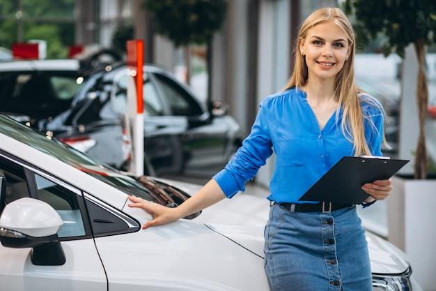Mulher de vendas em um showroom de carro