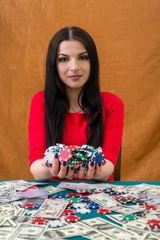 Mulher de vermelho com uma pilha de fichas de cassino nas mãos