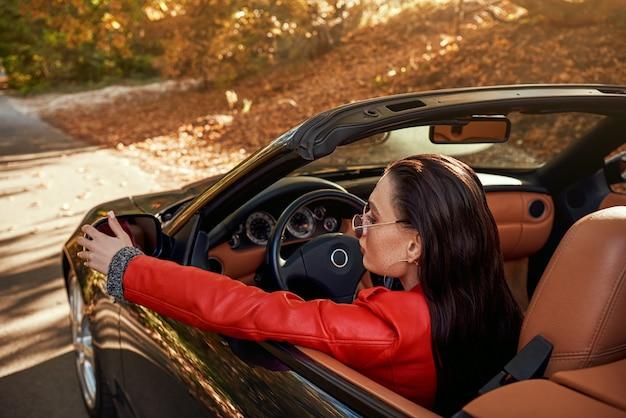 Mulher de vermelho em cabriolet ela usando óculos escuros retrovisores