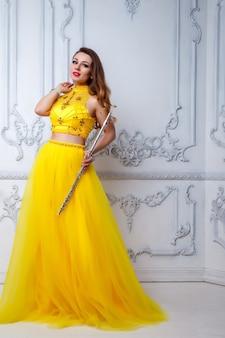 Mulher de vestido amarelo com flauta branca
