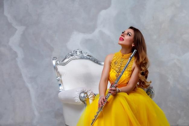 Mulher de vestido amarelo com flauta em fundo branco