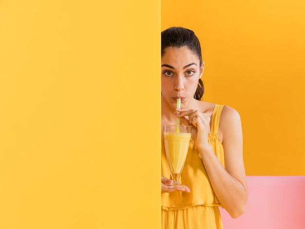Mulher de vestido amarelo com um copo de suco