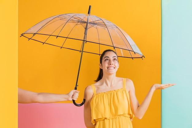 Mulher de vestido amarelo com um guarda-chuva