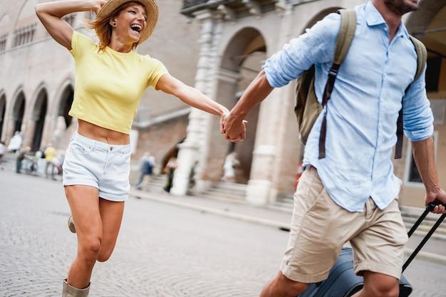 Mulher de vestido amarelo e chapéu segurando o homem correndo à mão na cidade de férias.