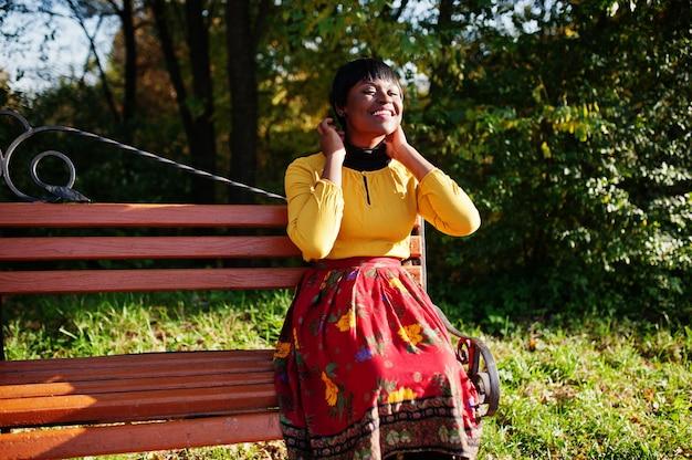 Mulher de vestido amarelo e vermelho no outono outono parque
