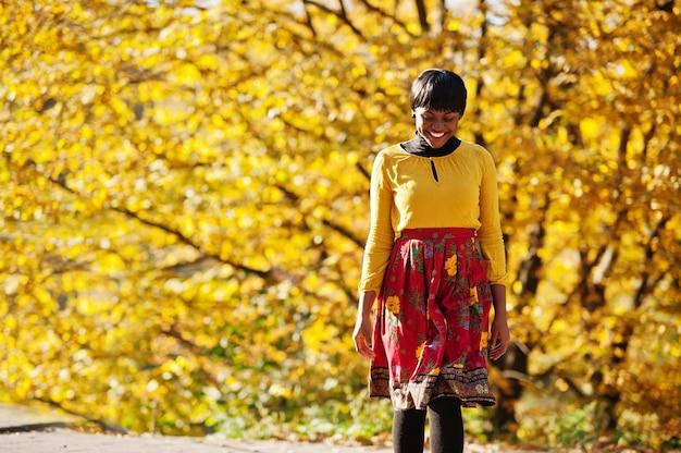 Mulher de vestido amarelo e vermelho no parque outono outono dourado