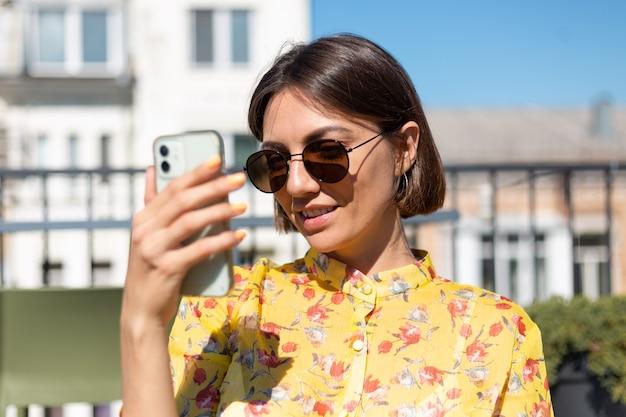 Mulher de vestido amarelo no terraço de um café de verão com telefone celular em dia de sol