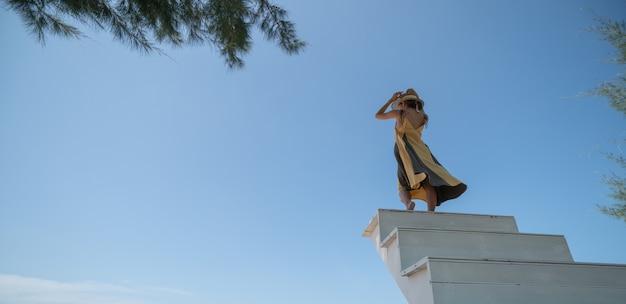 Mulher de vestido amarelo subindo na escada, no pôr do sol.
