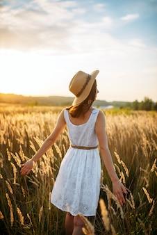 Mulher de vestido andando no campo de trigo ao pôr do sol
