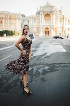 Mulher de vestido apertado no salto alto está de pé na estrada molhada em frente ao antigo prédio arquitetônico