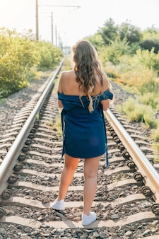 Mulher de vestido azul andando na vista traseira da ferrovia