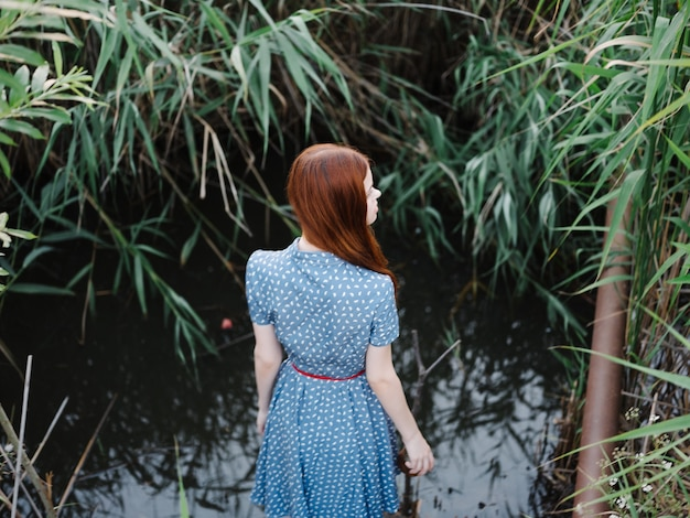 Mulher de vestido azul andar folhas verdes estilo de vida