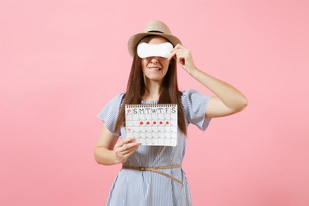 Mulher de vestido azul, chapéu segurando o absorvente higiênico, cobrir os olhos, calendário de períodos femininos para verificar os dias de menstruação isolados no fundo rosa. conceito médico, de saúde e ginecológico. copie o espaço