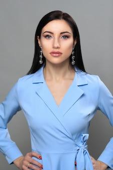 Mulher de vestido azul na moda e brincos