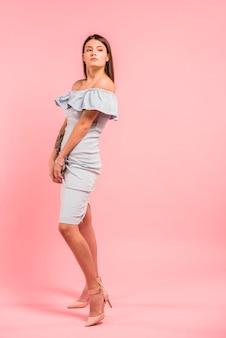 Mulher de vestido azul posando em fundo rosa