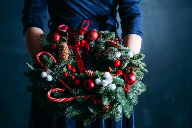 Mulher de vestido azul segurando guirlanda de natal artesanal decorada com bastões de doces.