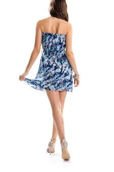 Mulher de vestido azul sem alças. vista traseira da jovem. design elegante de roupa de verão. modelo magro usa sapatos de salto.