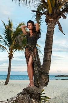 Mulher de vestido bonito com estampa de oncinha na praia
