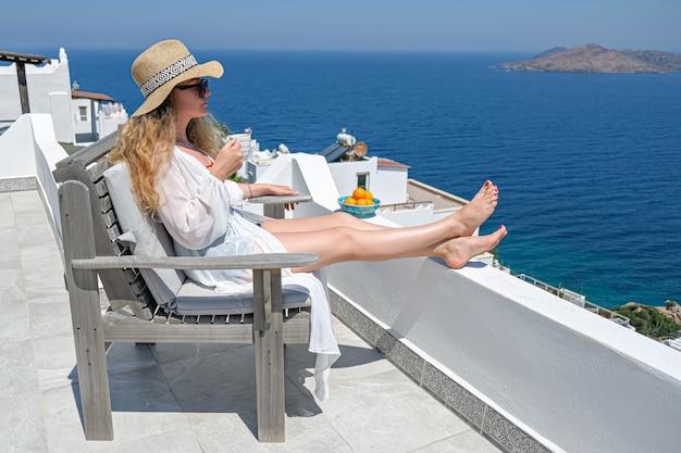 Mulher de vestido branco, chapéu de palha e xícara de café na varanda branca