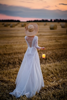Mulher de vestido branco com lâmpada nas mãos atravessa o campo após o pôr do sol