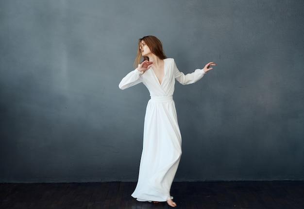 Mulher de vestido branco dançando posando glamour de performance