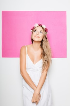 Mulher de vestido branco de algodão com flores no cabelo sorrindo