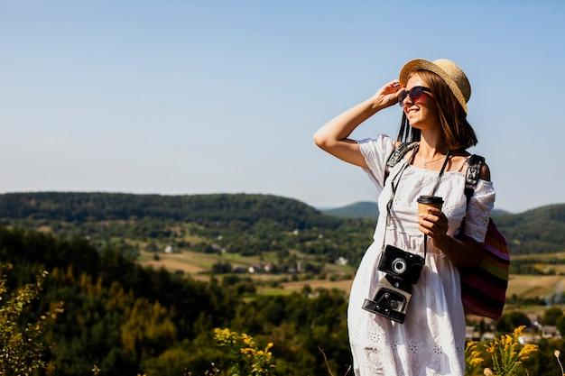 Mulher de vestido branco e câmera olhando para longe