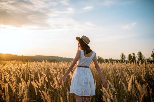 Mulher de vestido branco e chapéu de palha andando no campo de trigo no pôr do sol. mulher em um prado de verão, vista traseira