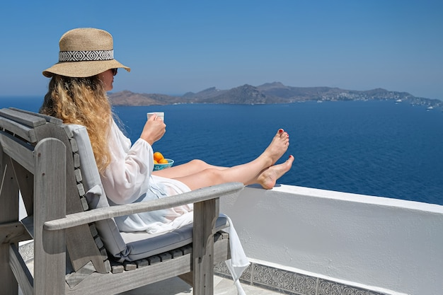 Mulher de vestido branco e chapéu de palha e xícara de café no terraço