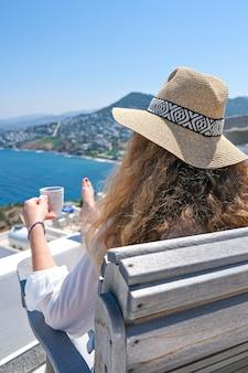 Mulher de vestido branco e chapéu de palha e xícara de café vista para o mar.