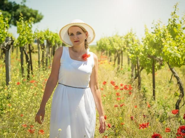 Mulher de vestido branco e chapéu nas fileiras dos campos de uva.