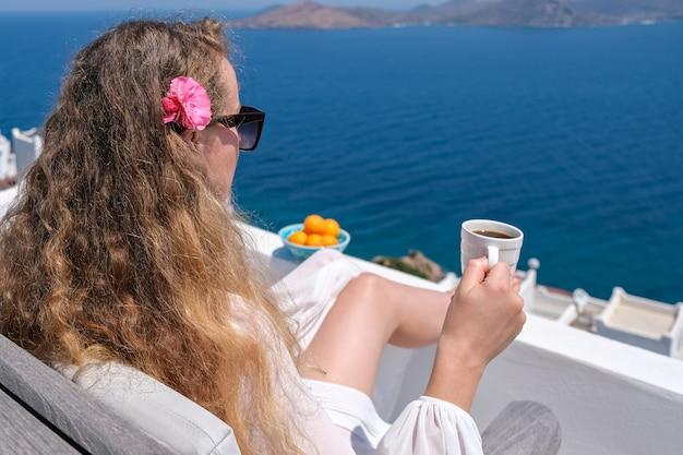 Mulher de vestido branco e flor no cabelo xícara de café na varanda branca