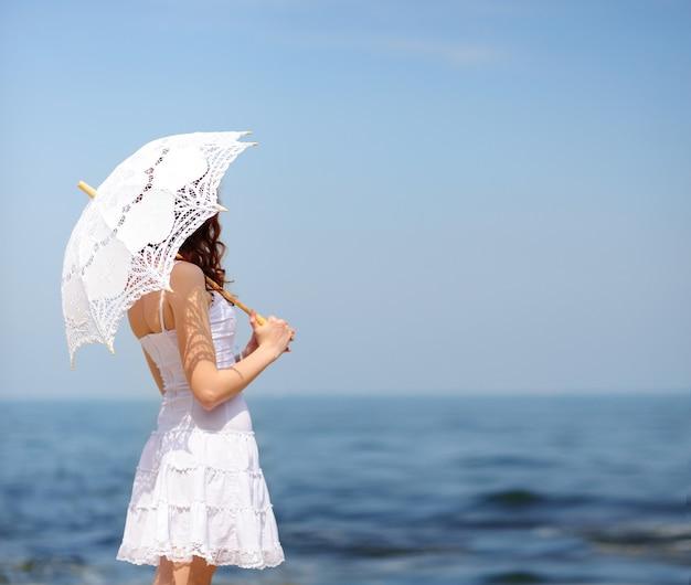 Mulher de vestido branco em uma praia de mar, escondendo-se do sol com guarda-chuva, sem rosto