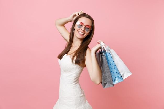 Mulher de vestido branco, óculos em forma de coração mantendo a mão perto da cabeça, olhando para trás segurando sacolas de pacotes multicoloridos com compras após as compras