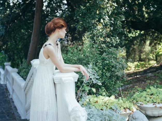 Mulher de vestido branco posando natureza princesa da grécia