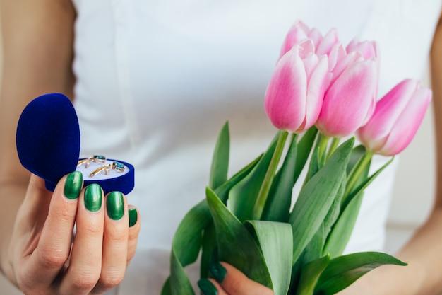 Mulher de vestido branco segurando tulipas cor de rosa e presentes