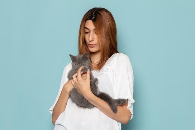 Mulher de vestido branco segurando um gatinho fofo cinza