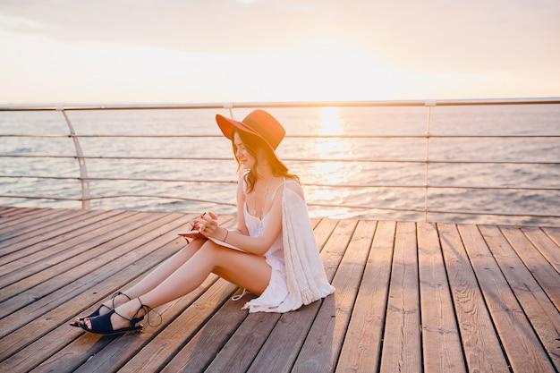 Mulher de vestido branco sentada à beira-mar ao nascer do sol pensando e fazendo anotações no livro diário