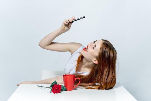 Mulher de vestido branco sentada à mesa tira uma selfie com o telefone.