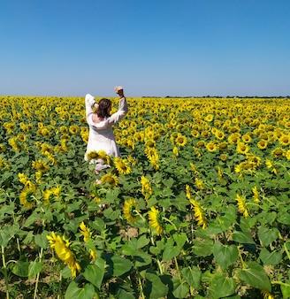Mulher de vestido branco vai para o campo de girassóis amarelos florescendo