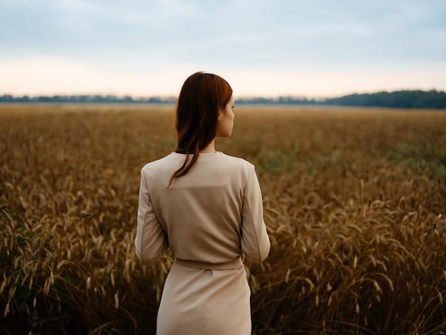 Mulher de vestido caminhada paisagem de trigo ar fresco
