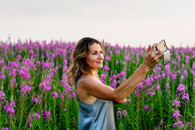 Mulher de vestido cinza tira foto de selfie no celular em um prado de erva-fogo