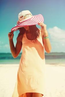 Mulher de vestido colorido, caminhando na praia