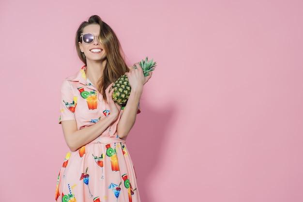 Mulher de vestido colorido, segurando um abacaxi