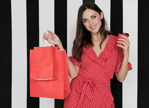 Mulher de vestido com café e sacolas de compras, sorrindo para a câmera