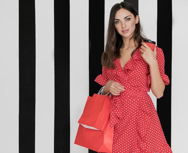 Mulher de vestido com café e sacolas de compras