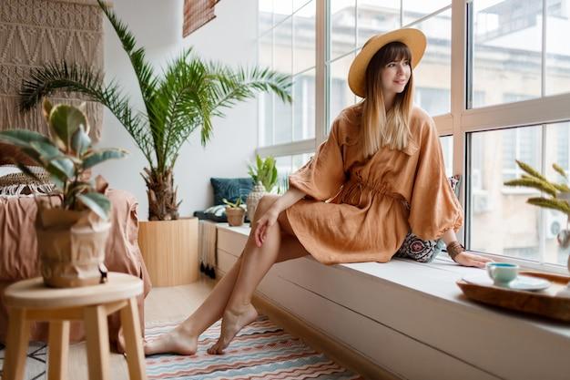 Mulher de vestido de linho, relaxando em casa, olhando a janela